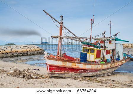 Fishing boat at dirty beach in bad air polutionConcept of Environment effect from petrochemical polution.