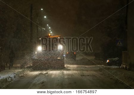 A snowplow cleaning streets in the aggravated traffic due to strong snowfall.