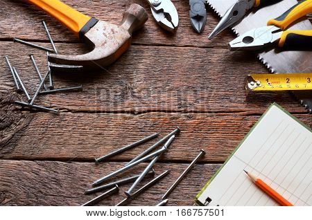 A top view image of several used hand tools on a wooden work bench.