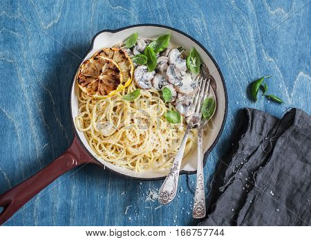Spaghetti with creamy mushrooms in a cast iron skillet on a blue background top view. Delicious lunch