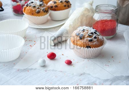 Vanilla cupcakes with chocolate chips and wipped cream in pastry bag