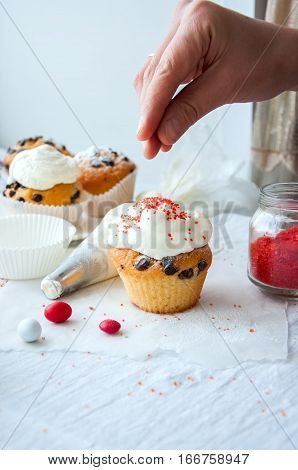 Vanilla cupcakes with chocolate chips and wipped cream frosting sprinkled with colored sugar and candies on the white background