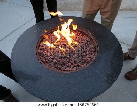 Several people standing around an outdoor flaming gas fire pit.