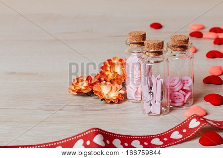 Valentine or holiday composition: view on bright small hearts spring flowers glass bottles contains clothespins and buttons and red ribbon with pattern on wooden background. Copy space for text.