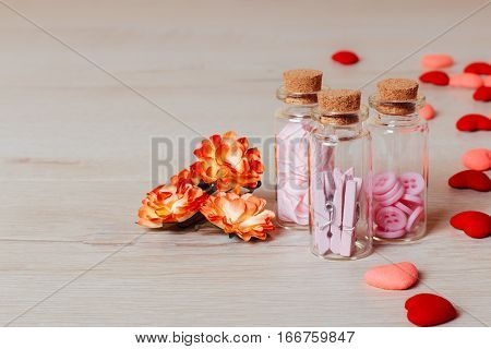 Valentine or holiday composition: view on bright small hearts spring flowers and glass bottles with clothespins and buttons on wooden background. Copy space for text.