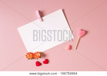 Valentine day composition: stationery / photo template with clamp small hearts candy and spring flowers on light pink background. Top view.