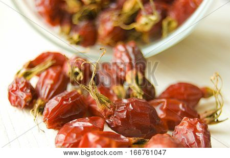 Dried rosehips scattered on the wooden table