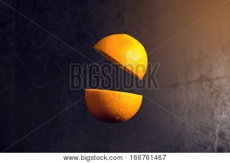 Knife And Orange Cut Are Frozen In Mid Air