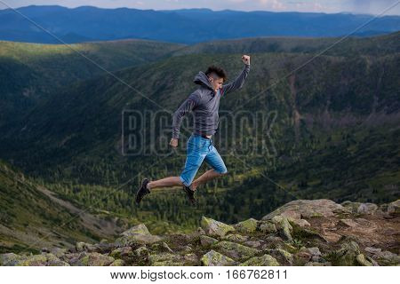 Man Jumping Celebrating Sucess With The View Of A Mountain