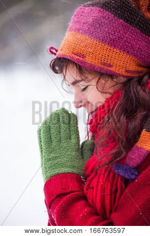 young woman meditate outdoor snow falls wearing woolen hat gloves and scarf closeup