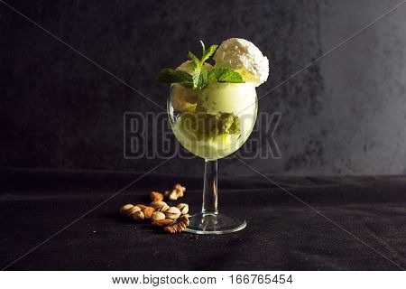 pistachio and vanilla ice cream with mint and grrn tea and nuts on black background poster