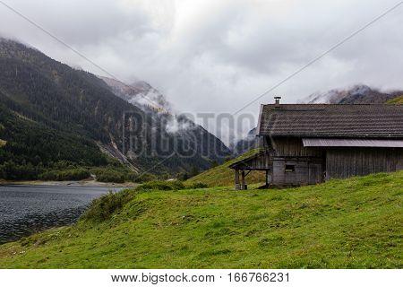 A path along a lake with farmhouse in Tirol, Austria.