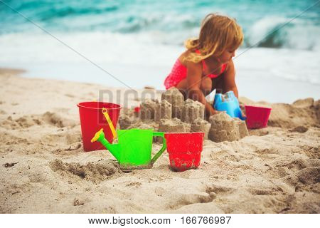 kids toys and little girl building sandcastle at beach