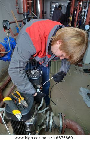 St. Petersburg Russia - March 5 2013: Repair pump heating system mechanic connects wires to electric motor.