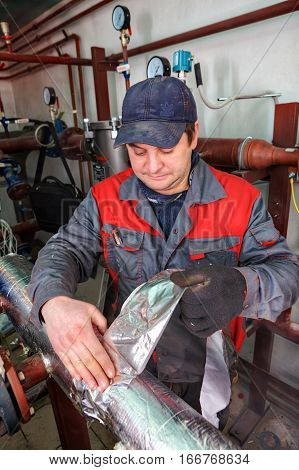 St. Petersburg Russia - March 5 2013: Heating engineer insulates pipe heating system in the boiler room using aluminum foil tape.