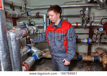 St. Petersburg Russia - March 5 2013: Mechanical Engineer in the process maintenance of the heating system in the basement of an apartment house.