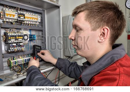 St. Petersburg Russia - March 5 2013: Maintenance Mechanic Electrician carries out repair the circuit breaker panel in industrial switchboard.