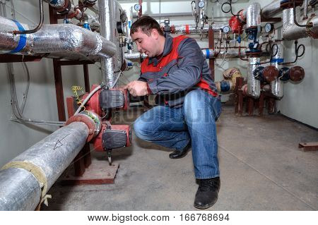 St. Petersburg Russia - March 5 2013: Technician maintenance repairman engineer inspecting heating system in boiler room.