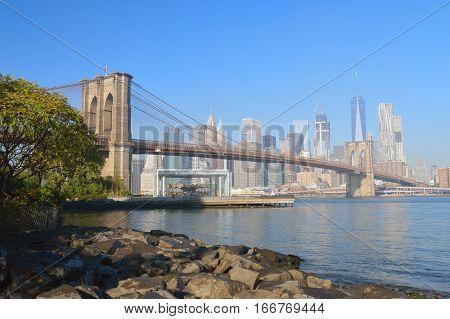 Manhattan skyline with Brooklyn Bridge at sunny day.