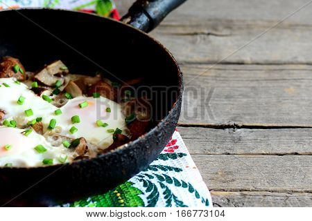 Fried eggs with mushrooms recipe. Fried eggs with mushrooms in a pan on vintage wooden background with copy space for text. Vegetarian breakfast idea. Closeup