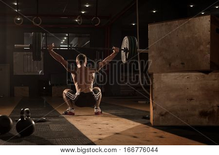 Muscular Man Doing Squats With Barbell Over Head