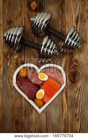 Proteins and dumbbells. Fish, cheese, eggs, meat, chicken and heart on wooden background