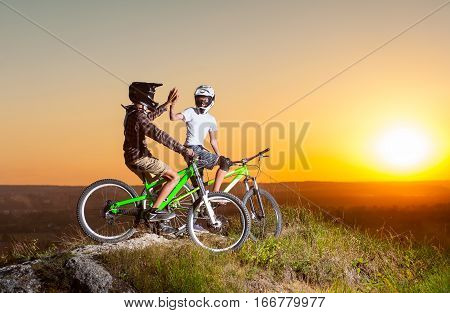 Cyclists With Mountain Bikes On The Hill In The Evening