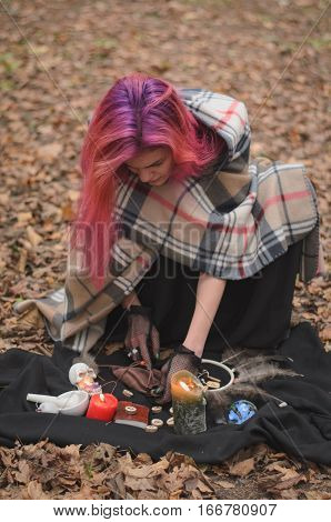 Young witch with pink hair is preparing to do witch craft with runes and candles and other strange things