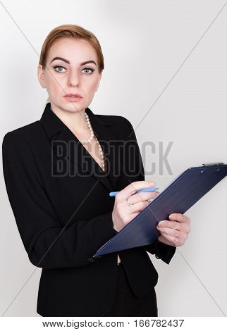 Attractive and energetic business woman holding pad for writing and takes notes.