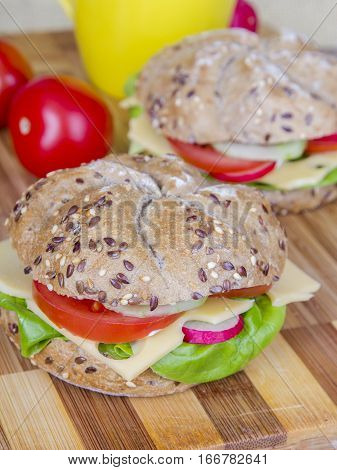 Vegetarian wholemeal sandwich with tasty vegetales on wooden background