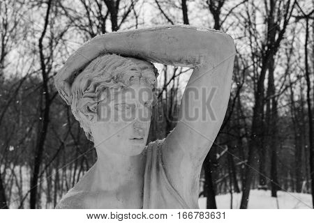 Sculpture Of A Girl In Winter Park Covered With Snow.