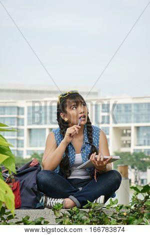 Creative college girl pondering over idea for essay