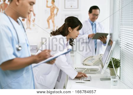 Vietnamese female doctor entering information in file on computer