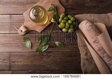 Green olives on a wooden board ciabatta olive oil bay leaf on wooden background. Ciabatta copyspace