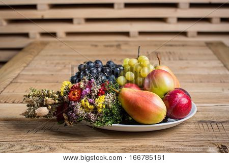 Fruit Plate With Wild Flower Decorations On The Wood Table