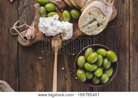 Green olives sliced ciabatta feta cheese on a wooden board. Spice. Garlic. Chees Feta. Ciabatta. Olives on a wooden background. Copyspace