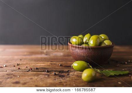 Green olives bay leaf on a wooden board. Olives on a black background. Copyspace