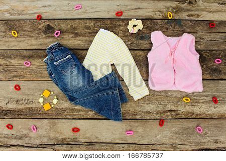 Children's clothing and accessories: jeans, hair clips, blouse, warm vest on old wooden background. Top view.