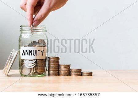 Hand putting coin in jar word annuity with money stack Concept business finance and investment