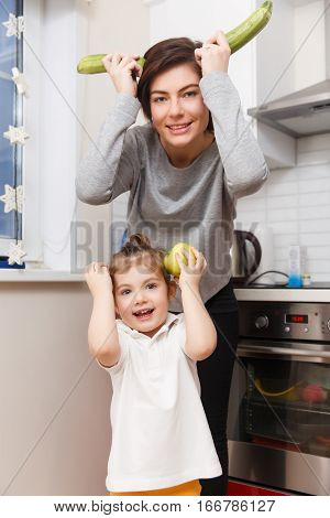 Brunette with daughter with zucchini and apples joke in kitchen