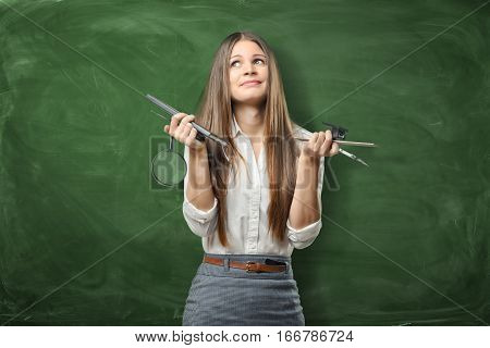 Confused businesswoman on green chalkboard background holding pens, a ruler and a magnifying glass in her hands. Business decisions. Workplace problems. Finding answers.