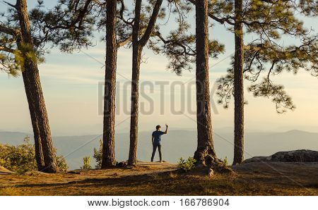 Moment of loneliness. Young Man standing alone in forest outdoor with sunset nature on background Travel Lifestyle and survival concept