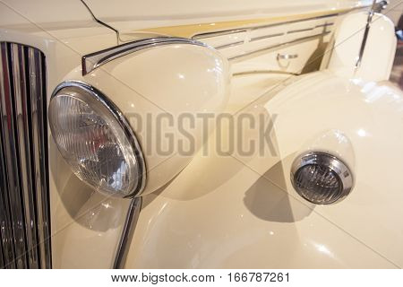 Side wheel headlamp and mudguard detail in a classic luxury car