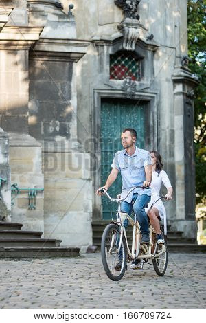Young Couple On Retro Tandem Bicycle At The Street City