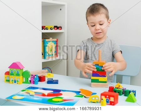 Child hands collect wooden puzzle on a table