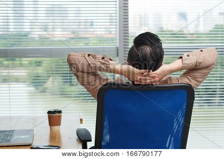 Rear view of business executive taking moment to relax in chair
