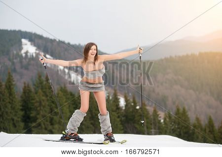 Active Naked Female Skier Having Fun On The Snowy Slope Of The Mountain, Wearing Ski Equipment