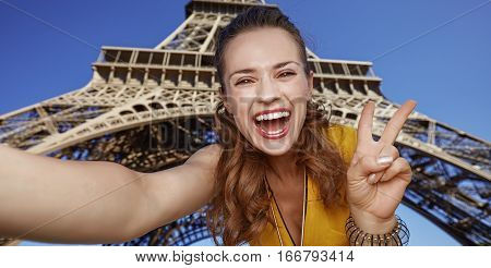 Woman Taking Selfie And Showing Victory Against Eiffel Tower