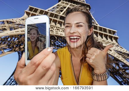 Woman Taking Selfie With Phone In Front Of Eiffel Tower In Paris