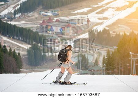 Active Female Skier Skiing On The Snowy Slope Of The Mountain, Wearing Ski Equipment, Backpack, Helm